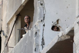 A man and a girl look out from a damaged building.