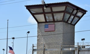 A razor wire-topped fence and watch tower at the US Naval Station in Guantánamo Bay, Cuba.