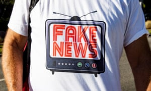 A Trump supporter wears a t-shirt reading 'Fake News'
