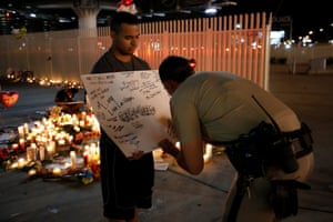 A police officer writes a message on a sign during a vigil on the Las Vegas strip
