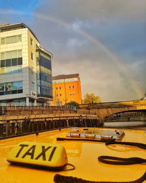 Roof of a yellow water taxi, with rainbow in the background