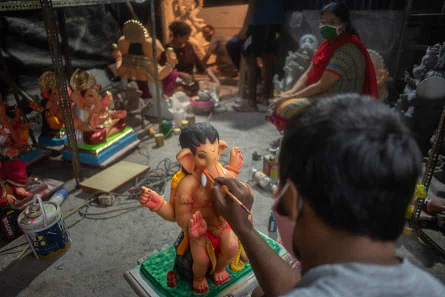 An artist paints a statue of Lord Ganesh.