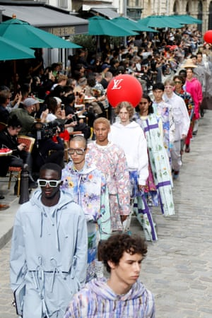 Louis VuittonPlace Dauphine, a gentle stroll from the Louis Vuitton HQ, played host to a street party for Virgil Abloh's third menswear collection. In front of guests gathered in the café-lined street, flowers were the main theme, as a metaphor for diversity. Floral prints and wildflower-covered hats and bags featured (they will be rendered in silk for production). Pastel ice-cream hued billowing trousers mixed with tailored jackets and sportswear pieces: to top things off, football's most fashionable player, Arsenal's Hector Bellerin, made a cameo appearance in a hot pink ensemble.