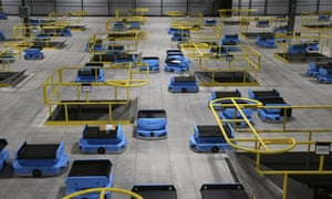 Amazon robots transport packages from workers to chutes at an Amazon warehouse in Goodyear, Arizona, 2019