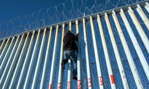A Central American migrant climbs the US-Mexico border fence in Playas de Tijuana, Baja California State, hoping to reach the US on 29 December 2018.