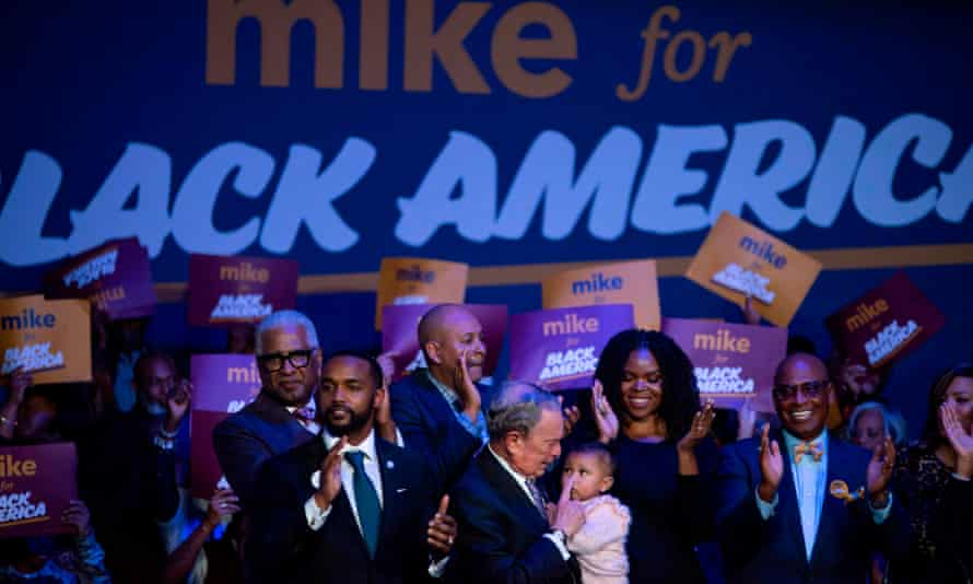 """Democratic presidential hopeful Mike Bloomberg (C) holds a baby during the """"Mike for Black America Launch Celebration"""" at the Buffalo Soldier National Museum in Houston, Texas."""