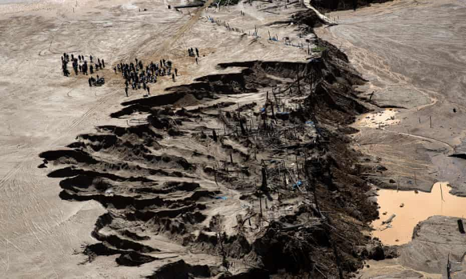 Police stand next to a crater created by gold miners during a police operation to eradicate illegal mining in an area known as La Pampa, in Peru's Madre de Dios region, in August 2015. Peruvian security forces blew up more than one hundred gasoline engines used to extract gold from the sandy soil.