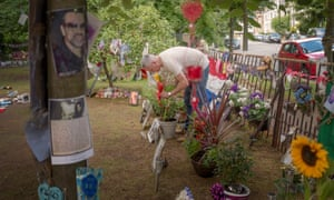 A George Michael fan lays tributes at the memorial outside his Highgate home.