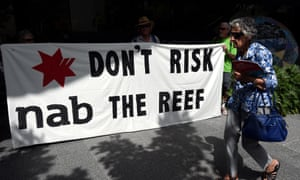 Protesters opposing the Abbot Point coal terminal hold up a sign as shareholders arrive for the National Australia Bank's annual general meeting in Brisbane, Thursday, Dec. 18, 2014