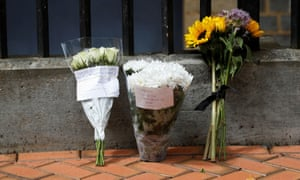 Flowers are seen near a police cordon at the scene of multiple stabbings in Reading, UK
