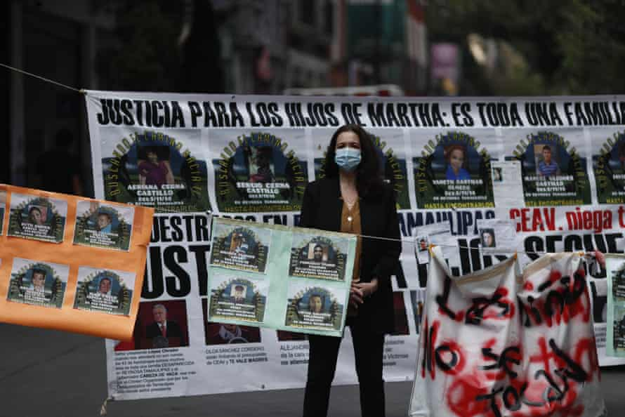 A journalist stands amid signs calling for justice for victims outside the human rights commission building in Mexico City on 8 September.