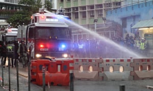 A police vehicle equipped with a water cannon clears the road from a barricade set up by protesters.