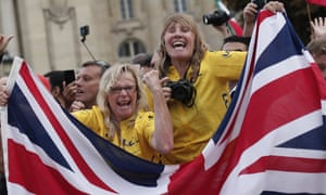 British fans wearing yellow hold the Union Jack at the presentation ceremony in Paris.