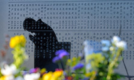 a man prays in Sendai, Miyagi, Japan, reflected on a stone memorial commemorating the 2011 tsunami.
