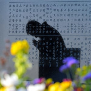 The shadow of a man praying for his colleagues shown on the stone memorial in Sendai, Miyagi