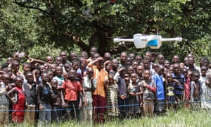 Children look on in astonishment as a drone is put through its paces at a community demonstration in Lilongwe