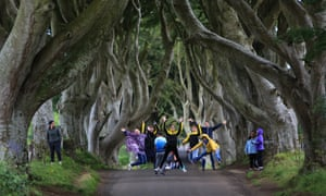 Tourists jump in the air at the Dark Hedges, County Antrim, Northern Ireland.