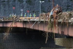 Aid workers walk through debris on Kuma bridge following torrential rain in Kumamoto prefecture