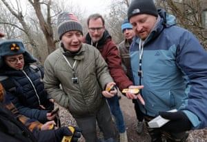 Tourists use geiger counters to check radiation levels as they visit the abandoned village of Zalissia in the Chernobyl exclusion zone