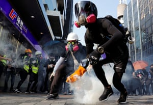 An anti-government demonstrator holds a teargas canister during a protest march in Hong Kong