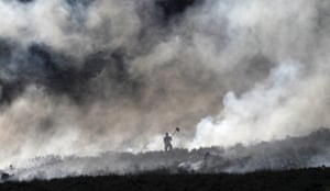A firefighter works at fire on a moor above Carrwood