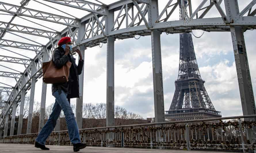 A woman walks past the Eiffel Tower in Paris