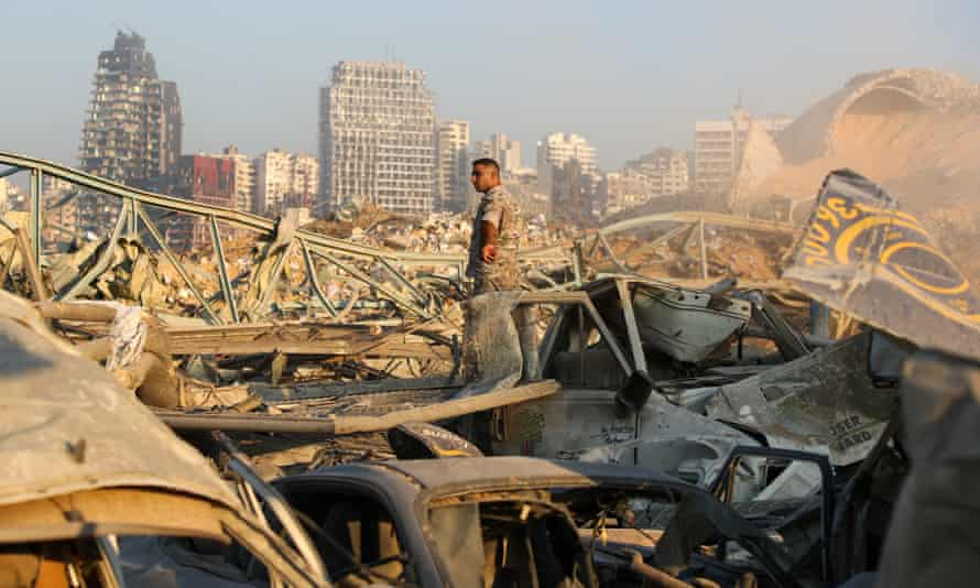 Man stands amid rubble and wrecked vehicles at the Port of Beirut