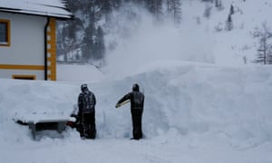 Two workers remove snow after a blizzard in the Austrian Alpine ski resort of Obertauern.