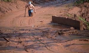 A man walks through the mud left by the dam burst in Barra Longo.