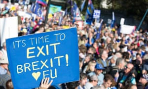 """In front of a march, a sign held up reads: """"It's time to exit Brexit! Love EU"""""""