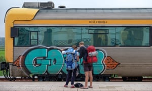 Backpackers standing in front of a train at a railway station