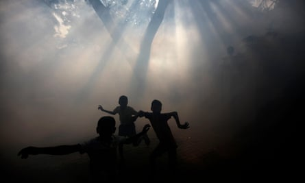 Boys play in smoke used to fumigate houses in Mumbai after an outbreak of dengue fever.