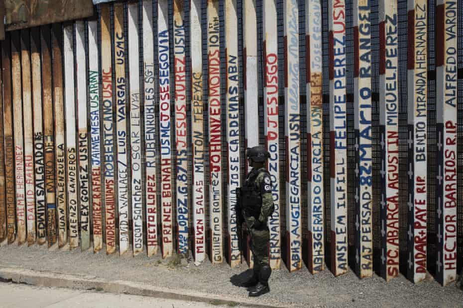 A member of Mexico's National Guard by a section of the US border wall where the names of deported US military veterans are listed, in Tijuana.