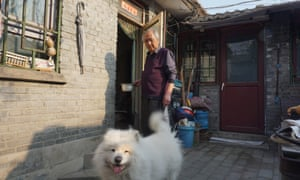 Zhou with his dog, Coconut, outside his house.