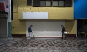 Shop owners spray disinfectant in Yokohama, Japan.