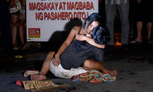 A dead Manila rickshaw driver, Michael Siaron, is embraced by his partner