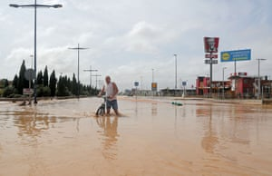 A man wades through a flooded street in San Javier, Murcia, in south-east Spain