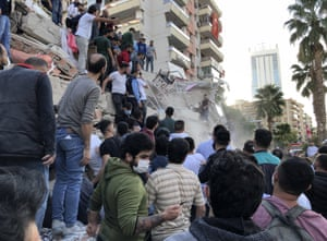 Rescue workers and local people try to save residents trapped in the debris of a collapsed building in İzmir