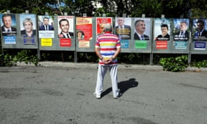 A man looks at campaign posters of the candidates running in the 2017 French presidential election.