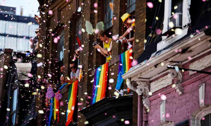 People throw confetti from their windows during a pride parade in Toronto.