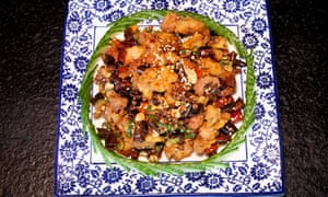 A square blue floral plate with a dish of chicken with dried chillies, ringed with slices of cucumber