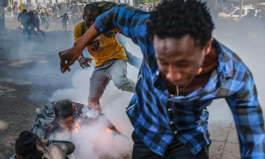 Students from the University of the Witwatersrand react to a police grenade during a protest against university fee increases.