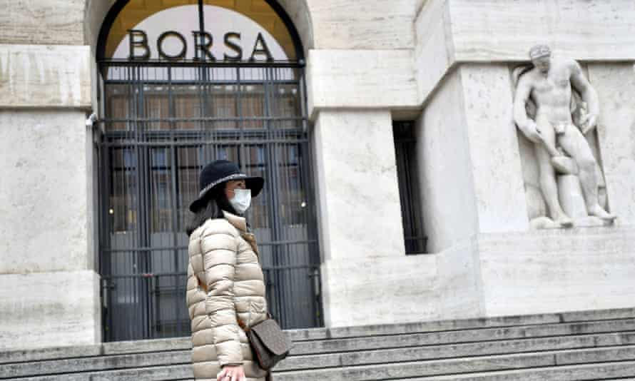 Woman in a face mask is seen in front of the Italian Stock Exchange.