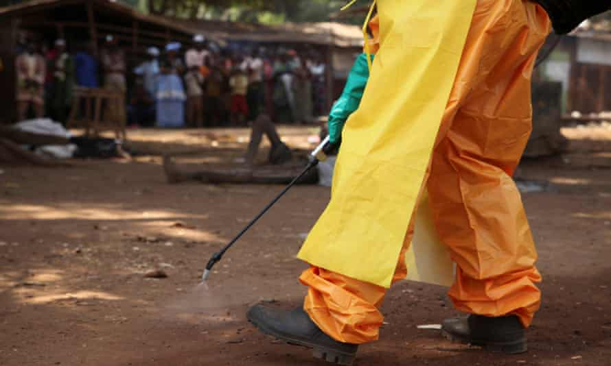 A member of the French Red Cross disinfects the area around a motionless person suspected of carrying the Ebola virus.
