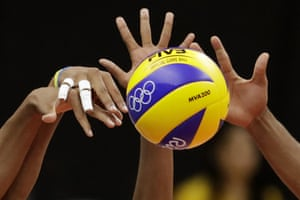 Members of team Cuba block a ball spiked by Russia's Egor Kliuka during a men's preliminary volleyball match.