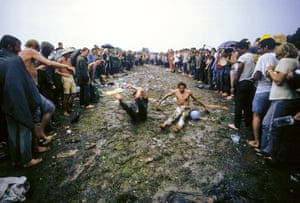 Crowd watching young men sliding in the mud. August 1969 ©Tom Miner / The Image Works