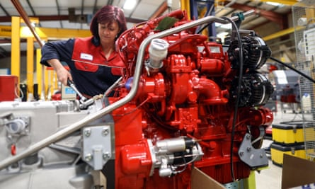 An employee works on the engine of an Enviro 200 bus at the Alexander Dennis Ltd factory in Guildford.