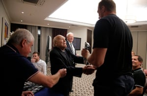"""During their first team meeting of the week, President of the Barbarians club, 92-year-old Micky Steele-Bodge,r hands out pins and ties to the players, here with 6'10"""" former All Black Dominic Bird."""