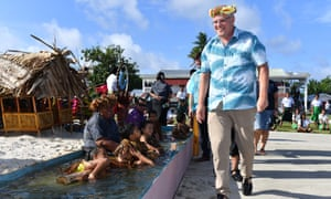 Children symbolically representing climate change greet Prime Minister Scott Morrison as he arrives for the Pacific Islands Forum in Tuvalu.