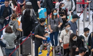 Travellers wearing face mask wait in line at an airport departure hall.
